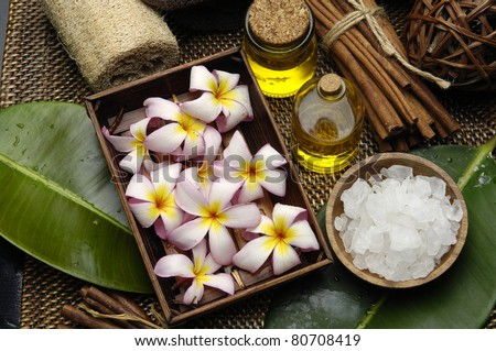 Spa wellness products � many frangipani in wicker basket with massage oil and salt on bowl and  green leaf on burlap mat