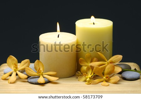 Spa with white candles and orchid on a black backdrop - stock photo