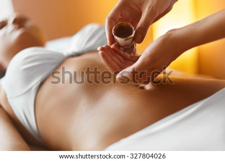 Spa woman.Aromatherapy oil massage. Masseur doing massage on beautiful young healthy caucasian woman body in  spa salon. Beauty treatment concept. Skincare, wellbeing, wellness, lifestyle. - stock photo