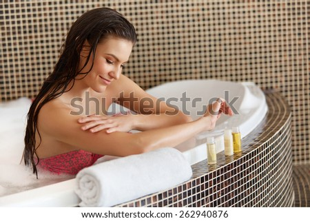 Spa Woman. Beautiful Woman in Bath Cares About Her Hands. Body care. - stock photo