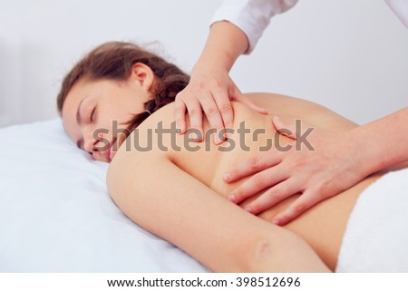 Spa Woman. Beauty Treatment. Beautiful Young Healthy Caucasian Girl Relaxing With Hand Massage Procedure In The Spa Salon. Masseur Massaging Her Back. Body Care. Skin Care, Wellness, Wellbeing. - stock photo
