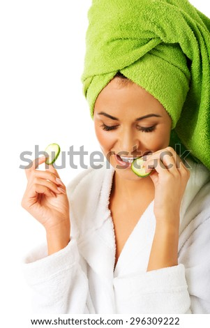 Spa woman in bathrobe eating cucumber. - stock photo