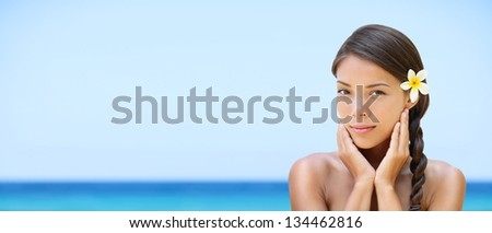 Spa woman on travel beach resort with perfect skin for beauty skin care. Beautiful mixed race Caucasian Asian ethnic girl looking serene a camera during holidays vacation. Panoramic banner on beach. - stock photo
