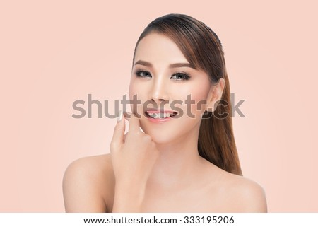 Spa Woman Portrait. Beautiful Asian Girl Touching her Face. Perfect Fresh Skin. Pure Beauty Model Female looking at camera. Youth and Skin Care Concept.on pink background with clipping path. - stock photo