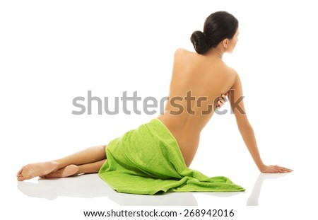 Spa woman sitting wrapped in towel back to camera.  - stock photo