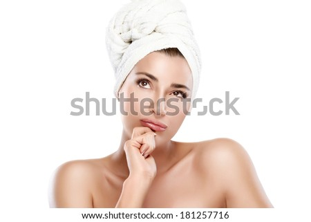Spa woman with towel on head gesturing looking up. Haircare and body care concept. Closeup portrait isolated on white