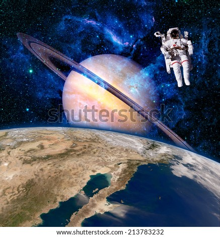 Space astronaut spaceman saturn planet surreal background. Elements of this image furnished by NASA. - stock photo