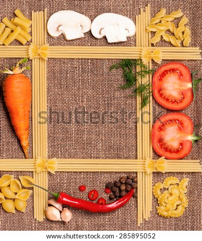 Space for recipes with pasta, vegetables, and spices on burlap - stock photo