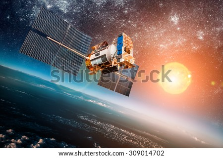 Space satellite orbiting the earth on a background star sun. Elements of this image furnished by NASA. - stock photo