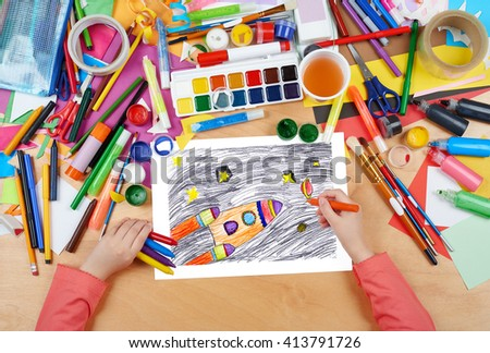 space ship fly and planet child drawing, top view hands with pencil painting picture on paper, artwork workplace - stock photo