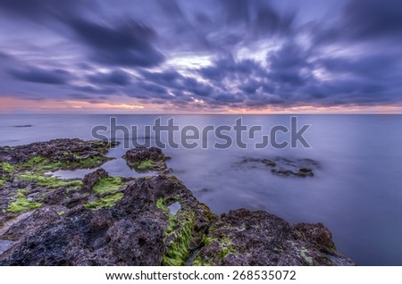 space vivid sunset over the tranquil mild oceanic rocky coastline - stock photo