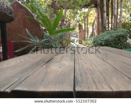 Space wooden table at garden background, product montage display.
