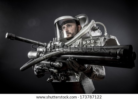Spacesuit, Astronaut on a black background with huge weapon. - stock photo