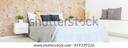 Spacious and bright bedroom interior with the marital bed with cushions, commode and wooden wall on a bedhead