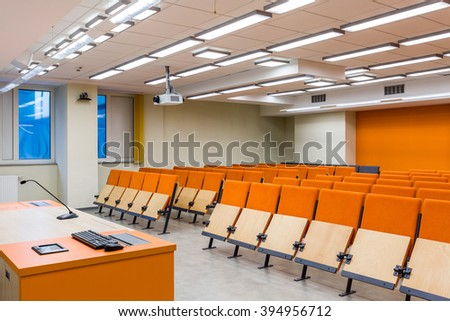 Spacious auditorium with orange, wood chairs and desk - stock photo