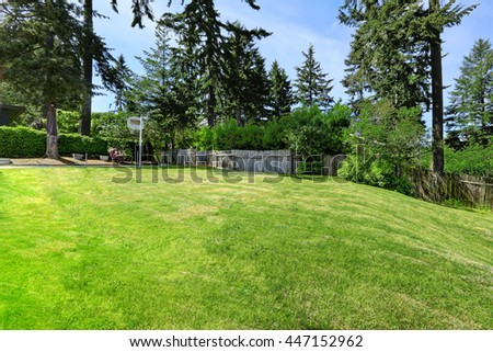 Spacious backyard area with wooden fence, green lawn and basketball court