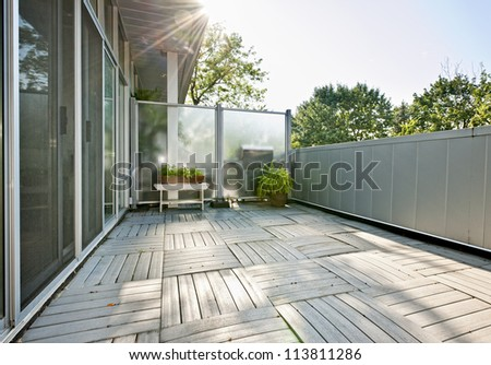 Spacious balcony of modern condo with plants on sunny day - stock photo