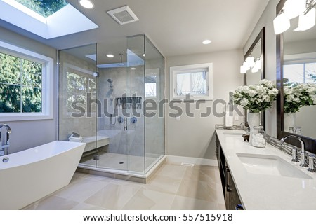 free standing tub and shower. Spacious bathroom in gray tones with heated floors  freestanding tub walk shower Bathroom Gray Tones Heated Floors Stock Photo 557515918