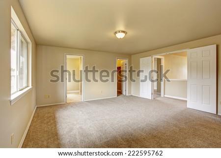 Spacious bright empty bathroom with carpet floor. Room has walk in closet and bathroom - stock photo