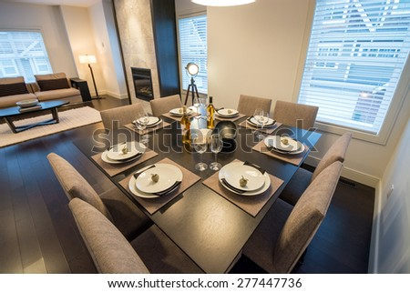 Spacious bright living room with a dining room table set for dinner. Interior design.