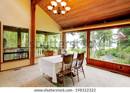 Spacious dining area in log cabin house with high vaulted ceiling and wide window. View of rustic dining table set.