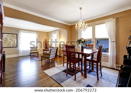 Spacious dining room with hardwood floor, pleated rug and wooden table set. View of living room