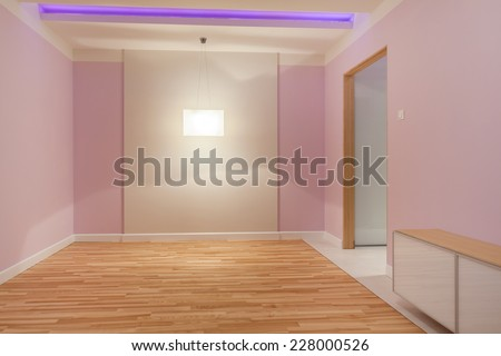 Spacious empty pink room with wooden flooring - stock photo