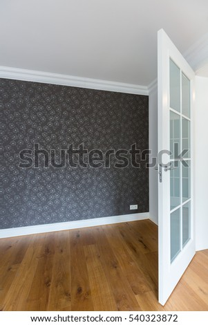 Spacious empty room with grey wallpaper in modern house