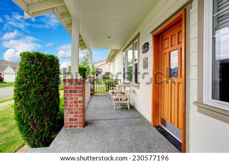 Spacious entrance porch with sitting area, railings and columns with brick trim - stock photo