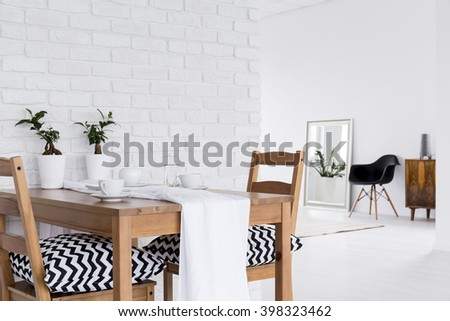 Spacious interior with wood table, chairs, mirror and decorative brick wall - stock photo