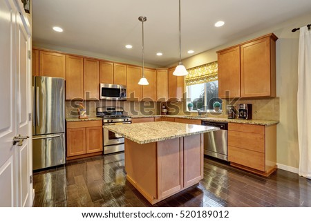 Spacious kitchen room with gleaming hardwood floor, kitchen island and stainless steel appliances. Northwest, USA