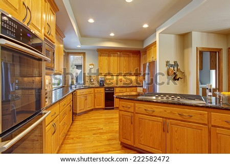 Spacious kitchen room with maple storage combination, kitchen island and built-in stove