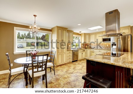 Spacious kitchen room with tile back splash trim and tile floor. Big kitchen island with built-in stove, granite top and steel hood. Dining area - stock photo