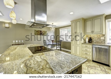 Spacious kitchen room with tile floor. Big kitchen island with built-in stove, granite top and steel hood - stock photo
