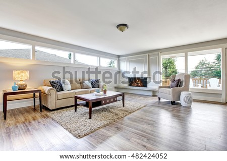 Spacious living room interior with polished hardwood floor, fireplace and dark brown coffee table. Northwest, USA