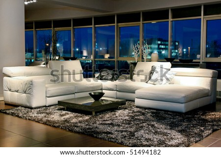 Spacious living room with beautiful view through glass wall - stock photo