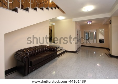 Spacious lobby with a ladder, mirrors and a sofa