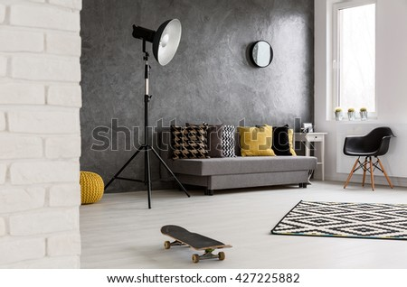 Spacious lounge in grey and white in modern flat. In the middle of room left skate board