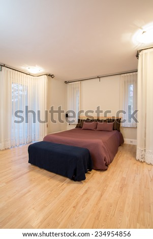 Spacious luxury bedroom interior with double comfortable bed - stock photo