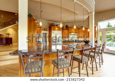 Spacious luxury kitchen room with columns and round granite counter top with stools - stock photo