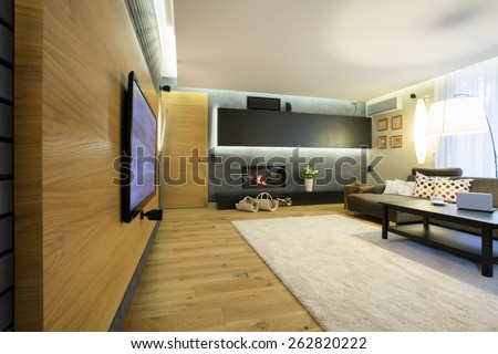 Spacious luxury lounge with big movie theater on wall - stock photo