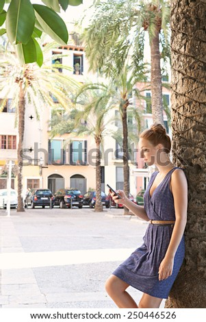 Spacious profile view of a young professional tourist woman visiting a destination city with palm trees, using a smartphone mobile phone on a summer holiday, outdoors. Travel and technology lifestyle. - stock photo