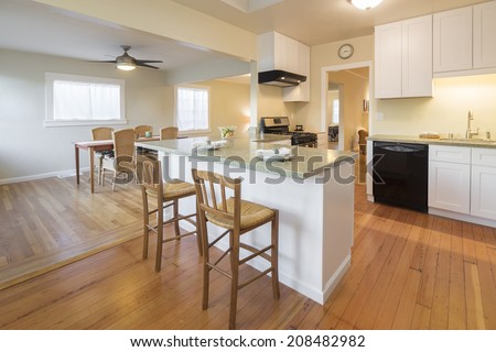 Spacious remodeled kitchen with breakfast bar and bar chairs.  - stock photo