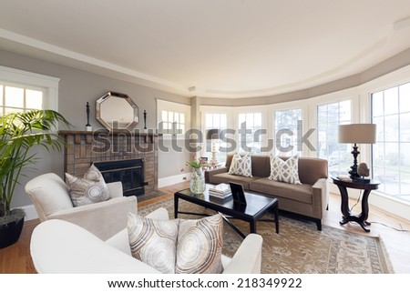 Spacious sitting area with living room in sumptuous style home with fitted fire place and wooden floor.  - stock photo