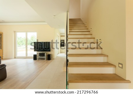 Spacious well lit living room with staircase - stock photo