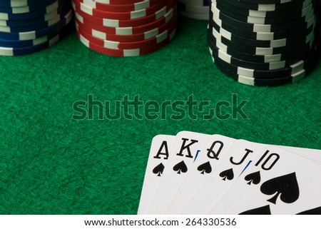 spades straight flush with poker chips on green table - stock photo