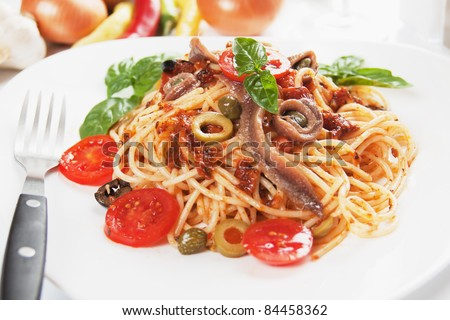 Spaghetti a la puttanesca with caper, anchovy and olives - stock photo