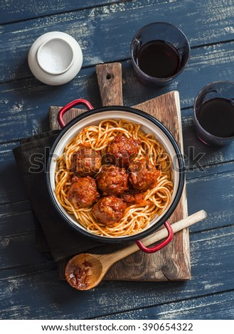 Spaghetti and meatballs in tomato sauce and two glasses with red wine on wooden rustic board. Delicious lunch - stock photo