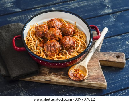 Spaghetti and meatballs in tomato sauce on wooden rustic board. Delicious lunch - stock photo