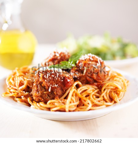 spaghetti and meatballs with oil and salad - stock photo